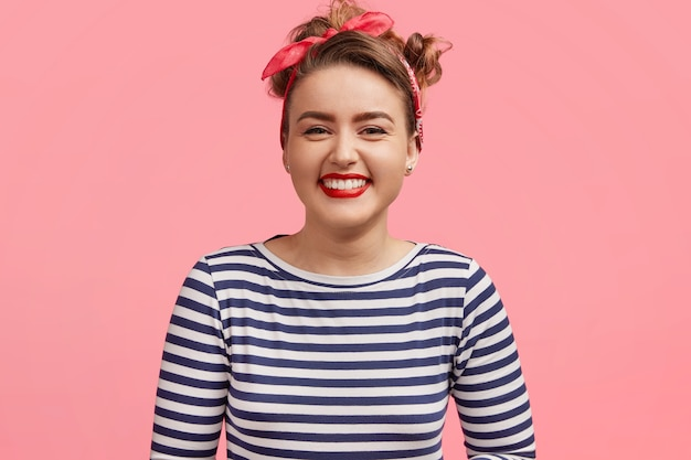 Mensen en geluk concept. schattige jonge glimlachende vrouw gekleed in zeemans trui, blij met aangenaam verhaal, staat tegen roze muur. blij pinupmeisje spreekt positiviteit uit