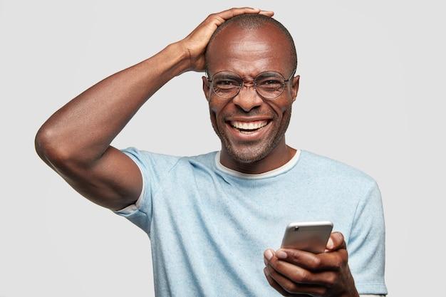 Mensen en geluk concept. vrolijke kale man giechelt en houdt de hand op het hoofd, houdt moderne slimme telefoon vast