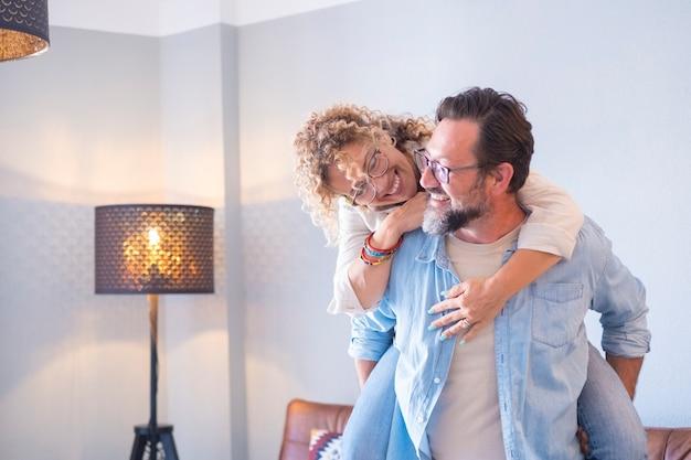 Mensen en gelukkig vrije tijd indoor concept gelukkige mensen paar man en vrouw op de rug hebben plezier en genieten samen van het huis glimlachen en lachen veel volwassen kopen flat en vieren dolblij