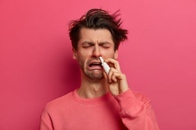 Mensen en gezondheidszorgconcept. noodlijdende man gebruikt neusdruppels, heeft een loopneus, gezwollen rode ogen, symptomen van een epidemische ziekte, geneest met een goede remedie, heeft een zwak immuunsysteem, verkouden in de winter