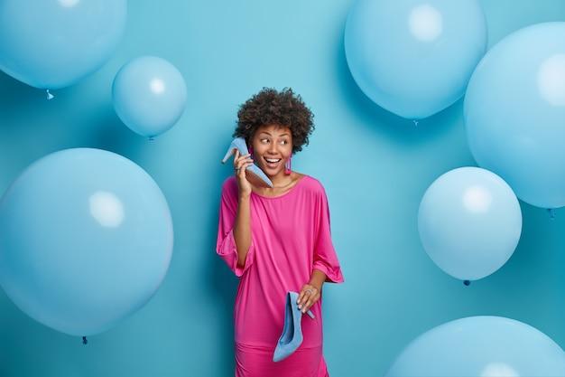 Mensen en kledingconcept. vrolijke modieuze vrouw in roze gekostumeerd, houdt schoenen met hoge hakken vast, imiteert telefoongesprek, kleedt zich voor feest, demonstreert haar moderne garderobe. blauwe muur