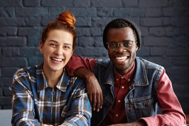 Mensen en levensstijl concept. aantrekkelijke jonge man met bril en stijlvolle hipster zwarte hoed zijn elleboog leunend op de schouder van zijn mooie roodharige vriendin tijdens bijeenkomst in coffeeshop
