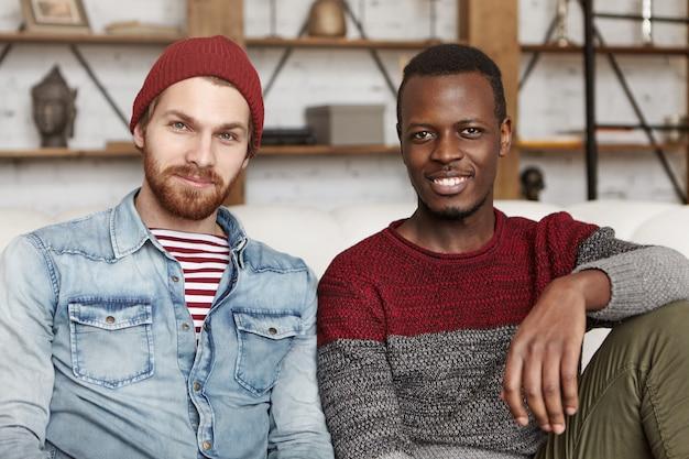 Mensen en levensstijl concept. twee gelukkige jonge mannen van verschillende etnische groepen samen tijd doorbrengen, zittend op de bank dicht bij elkaar. stijlvolle witte man in hoed binnenshuis rusten met zijn zwarte vriend