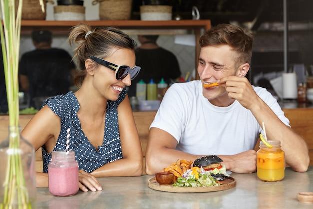 Mensen en levensstijl concept. twee vrienden hebben een leuk gesprek genieten van lekker eten tijdens de lunch. jonge man frietjes eten en praten met zijn aantrekkelijke vriendin in stijlvolle zonnebril