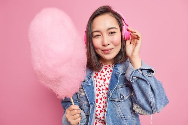 Mensen en levensstijl concept. vrij aziatisch tienermeisje luistert naar muziek via een koptelefoon met heerlijke suikerspin gekleed in een modieus spijkerjasje en geniet van vrije tijd geïsoleerd over roze muur