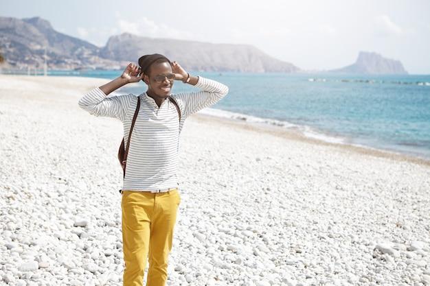 Mensen en levensstijl. reizen en toerisme. knappe vrolijke jonge afro-amerikaanse mantraveler die modieuze kleding en toebehoren draagt die zich op kiezelstrand bevinden, die mooi marien mening bewonderen