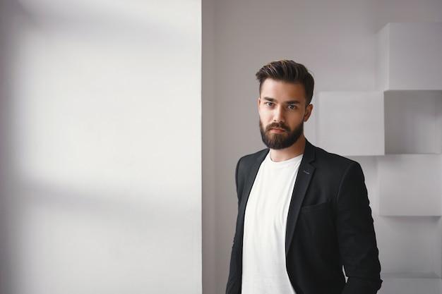 Mensen en levensstijlconcept. elegante jonge brunette ongeschoren zakenman gekleed in een stijlvolle jas over wit t-shirt poseren geïsoleerd bij het raam, camera kijken met ernstige gezichtsuitdrukking