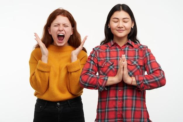 Mensen en levensstijlconcept. meisje schreeuwt van woede terwijl haar vriend kalm mediteert, handen vouwt in het namaste-teken. gele trui en geruit overhemd dragen. tribune geïsoleerd over witte muur
