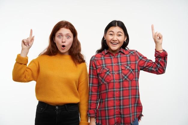 Mensen en levensstijlconcept. twee gelukkige, geschokte meisjes. gele trui en geruit overhemd dragen. en wijst op kopie ruimte, geïsoleerd op een witte muur
