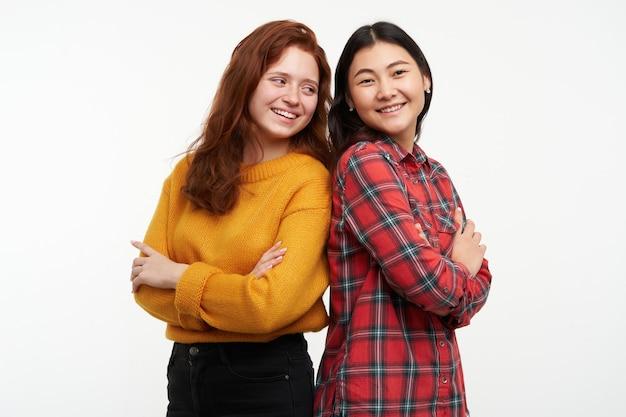 Mensen en levensstijlconcept. twee gelukkige meisjes. gele trui en geruit overhemd dragen. sta rug aan rug en houd de armen gekruist. geïsoleerd over witte muur