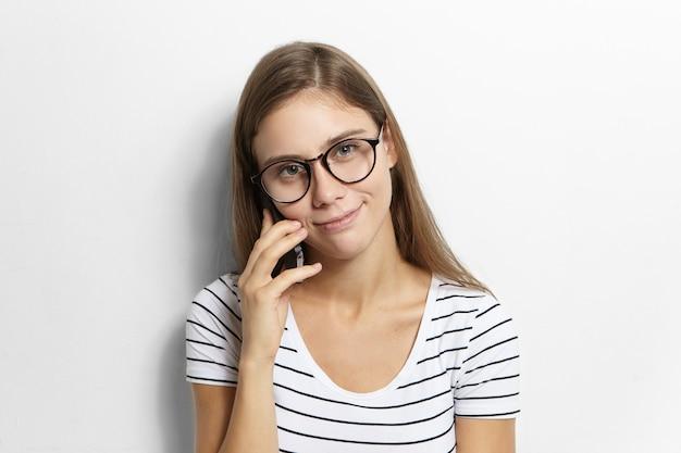Mensen en moderne elektronische gadgets concept. leuke europese tienermeisje in gestreept t-shirt en bril genieten van telefoongesprek met beste vriend, jongens, roddels en huiswerk bespreken