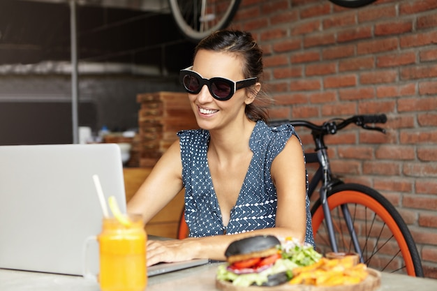 Mensen en moderne technologie. mooie vrouw die in modieuze zonnebril van vrije wifi-zitting voor open laptop met voedsel op lijst genieten. vrouwelijke freelancer die notitieboekjecomputer voor het verre werk gebruikt