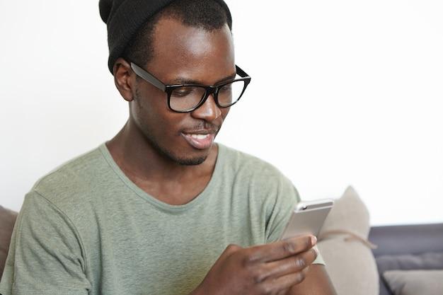 Mensen en moderne technologieën concept. knap jong afrikaans mannetje die van online mededeling genieten die snelle internetverbinding met hoge snelheid op smartphone gebruiken terwijl thuis het ontspannen op weekend