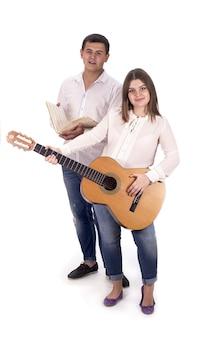 Mensen en muziek. zwangere vrouw en man in witte overhemden en jeans met gitaar op witte achtergrond