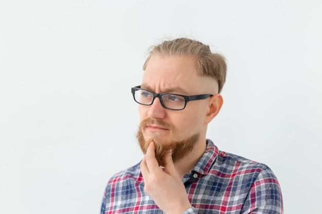 Mensen en negatieve emoties concept - bebaarde man in glazen hard nadenken over iets