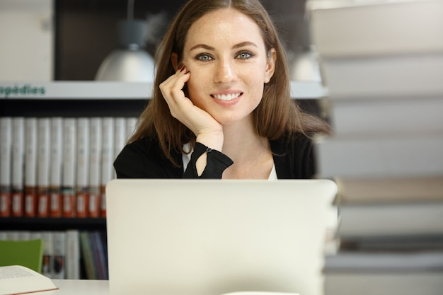 Mensen en onderwijs. mooie blanke vrouwelijke leraar lacht, kijkt blij en tevreden, laat haar elleboog op tafel rusten, werkt aan notitieboekje, leest leerboeken terwijl ze zich voorbereidt op een lezing in de bibliotheek