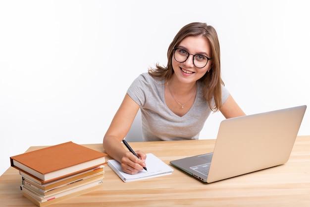 Mensen en onderwijsconcept. gelukkig vrouwelijke student zittend aan de houten tafel met laptop