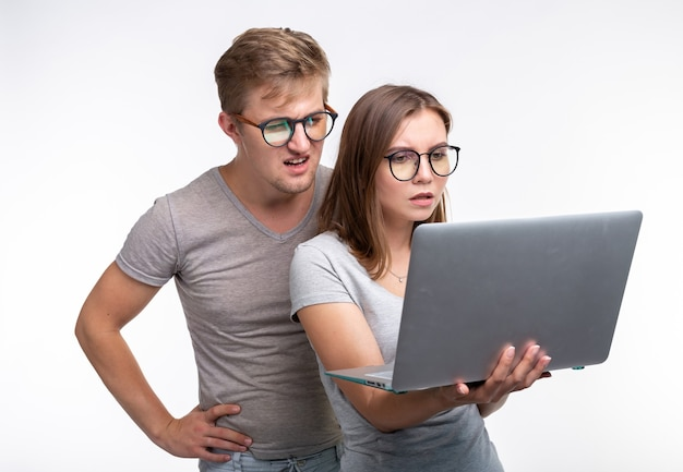 Mensen en onderwijsconcept. twee jonge student die in laptop over witte achtergrond kijkt