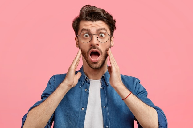 Mensen en onverwachte concept. geschokte jonge man met stoppels, opent mond wijd, houdt handen op wangen, merkt iets ongelooflijks op, draagt ronde bril en spijkerblouse, staat binnen
