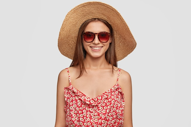 Mensen en rust concept. heerlijk tevreden vrouwelijke toerist in trendy tinten, zomerhoed en jurk. toerist heeft vakantie