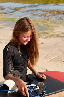Mensen en rust concept. verticaal schot van vrolijke surfboarder in zwarte wetsuit
