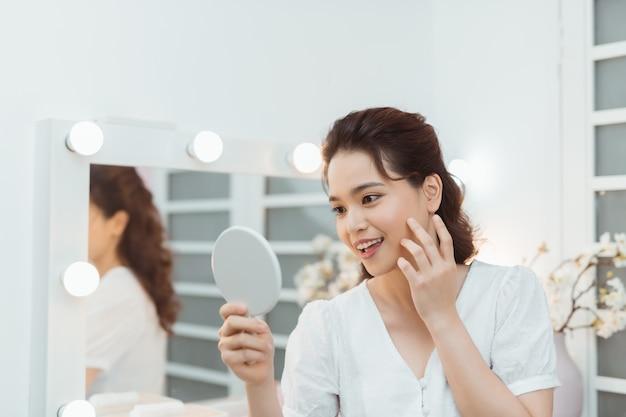 Mensen en schoonheid concept - mooie vrouw met spiegel aanraken van haar gezichtshuid thuis slaapkamer