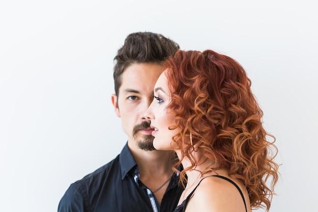 Mensen en schoonheidsconcept - hoofd geschoten portret van paar met ernstige gezichten over witte muur