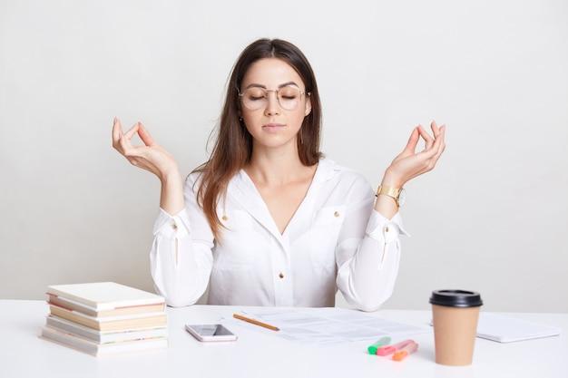 Mensen en spiritualiteit concept. ontspannen brunette jonge vrouw vormt op de werkplek in mudra teken, geniet van een rustige sfeer, trekt zichzelf samen en bereidt zich voor op het werk, drinkt afhaalkoffie