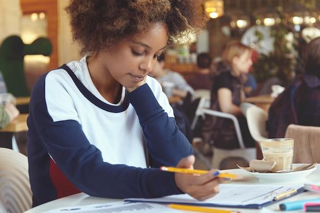 Mensen en technologie. geconcentreerde donkere vrouwelijke freelancer bezig met touchpad, iets opschrijven in vel papier.