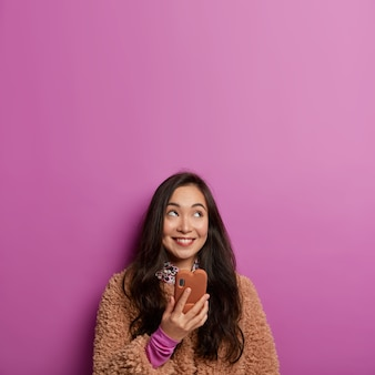 Mensen en technologieën concept. dromerig mooi donkerharig meisje houdt mobiele telefoon in de hand, stuurt spraakbericht naar vriend, hierboven geconcentreerd met een glimlach
