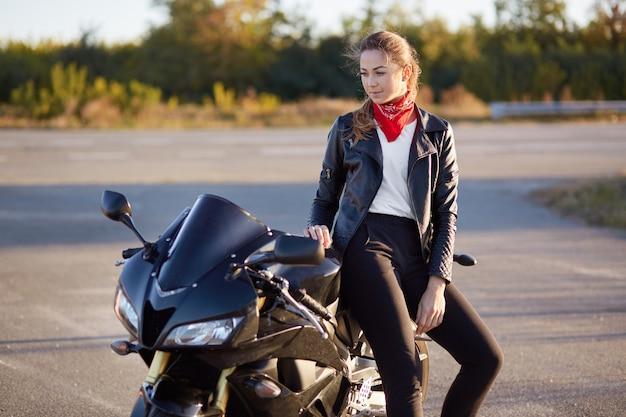 Mensen en transport concept. mooie jonge vrouw in zwarte stijlvolle motorrijderskleding, leunt op snelle motor, heeft doordachte expressie, poseert alleen op de weg, geniet van rustige sfeer en snelheid