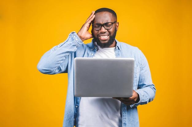 Mensen en vermoeidheid concept. de vermoeide zwarte afro-amerikaanse man zet een bril af, voelt zich slaperig en overwerkt, omringd door moderne technologieën.