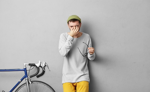 Mensen en vermoeidheid concept. jonge aantrekkelijke man met dikke baard, gekleed in modieuze kleding, zet zijn bril af en krabt ogen, moe na een lange reis alleen met de fiets