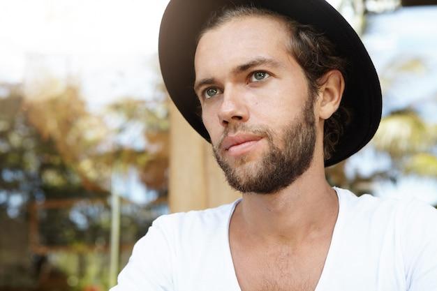 Mensen en vrije tijd. headshot van modieus jong mannetje met trendy baard die zwarte hoed dragen die nadenkende uitdrukking hebben, die afstand onderzoeken, dag plannen