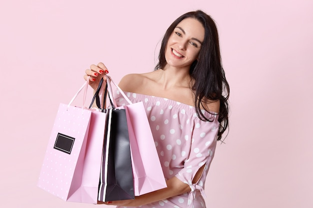 Mensen en winkelen concept. gelukkig donkerharige vrouw shopaholic gekleed in polka dot jurk, draagt boodschappentassen, geïsoleerd op roze, heeft rode manicure. vrouwelijke klant staat binnen