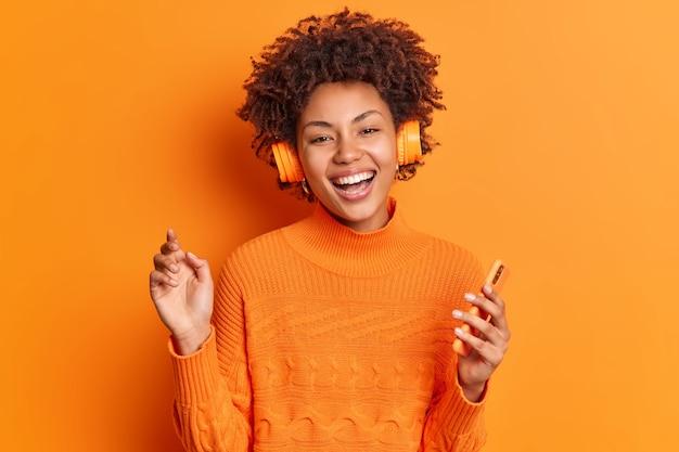 Mensen entertainment en hobby concept. vrolijke jonge afro-amerikaanse vrouw met krullend haar houdt moderne smartphone luistert naar muziek via stereohoofdtelefoon vormt tegen levendige oranje achtergrond