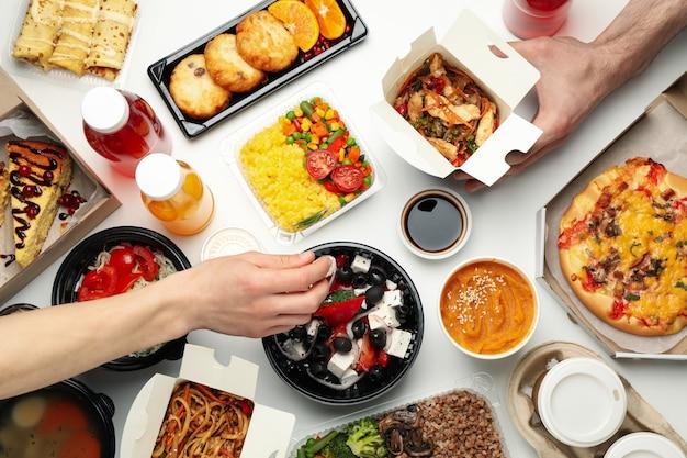 Mensen eten afhaalmaaltijden. voedsellevering. lekker eten op witte tafel