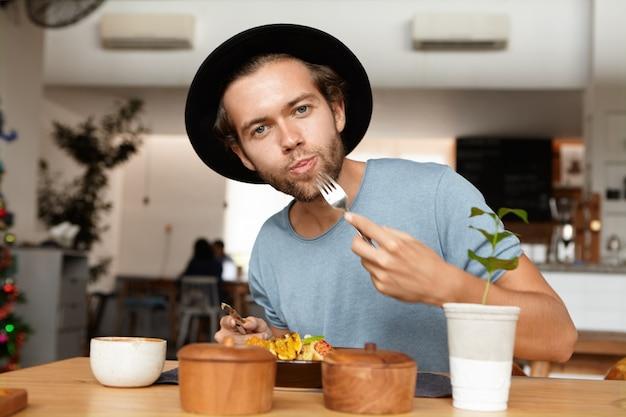 Mensen, eten en lifestyle concept. binnenschot van aantrekkelijke jonge student die zwarte hoed en blauwe t-shirt draagt die zijn honger kalmeert