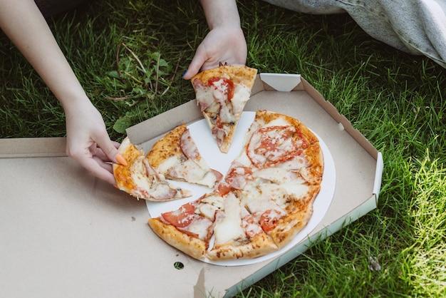 Mensen eten fastfood. handen van vrienden die plakjes pizza nemen niet gezond eten. zachte selectieve focus.