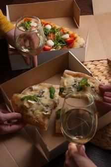 Mensen eten italiaanse pizza met witte wijn. concept: eten bezorgen