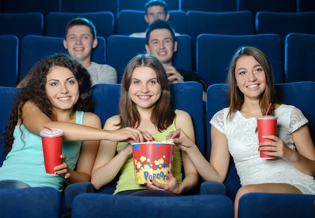 Mensen eten popcorn en drinken frisdrank tijdens het kijken naar film