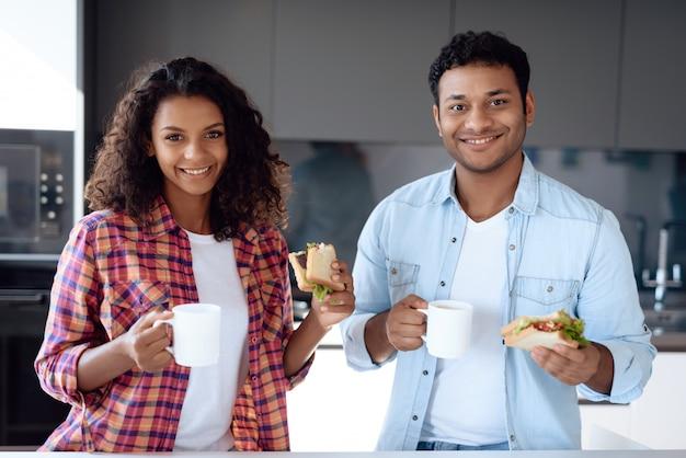 Mensen eten sandwiches en drinken koffie.