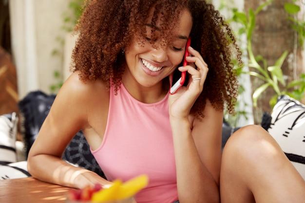 Mensen, etniciteit en communicatieconcept. donkere huid jonge schattige afro-amerikaanse vrouw geniet van telefoongesprek met vriend of minnaar, zit alleen tegen gezellig binnenlands interieur.