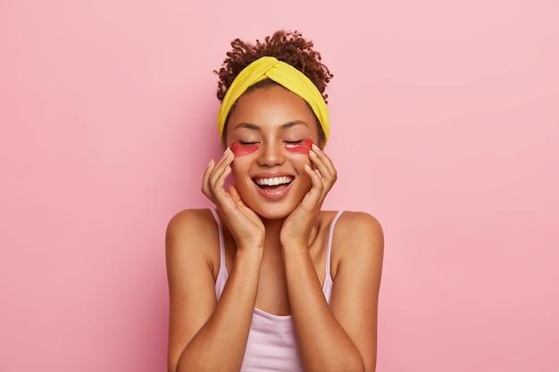 Mensen, etniciteit, plezier, schoonheid en tevredenheid. vrolijke, donkere jonge vrouw past hydrogelvlokken toe, vermindert rimpels en donkere kringen, draagt gele hoofdband op het hoofd, heeft een frisse huid