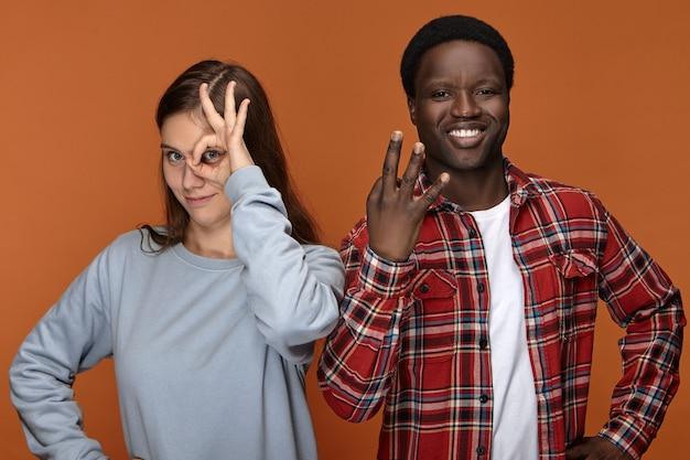 Mensen, etniciteit, vriendschap en liefde. emotionele grappige jonge zwarte man gebaren en glimlachen, staande naast zijn witte vriendin die door cirkel tussen vingers