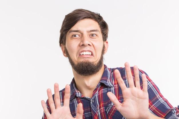 Mensen, expressie en gebaar concept - jonge man met stop gebaar op witte achtergrond