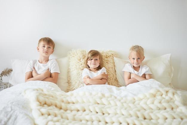 Mensen, familie en jeugdconcept. drie kinderen zitten naast elkaar op een groot wit bed met de armen over elkaar en kijken naar tekenfilms op weekendochtend. twee broers en zus spelen thuis