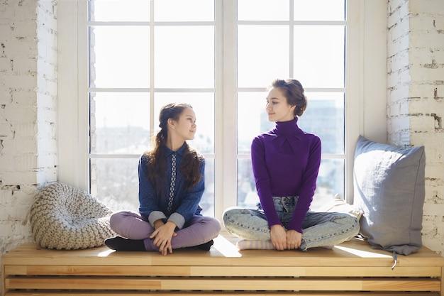 Mensen, familie, geluk en relaties concept. binnen schot van gelukkige jonge vrouw vrije tijd doorbrengen met haar dochter thuis