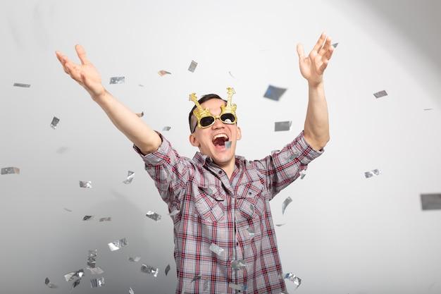 Mensen, feestdagen en partij concept - grappige kerel in glazen dansen in confetti op witte muur.