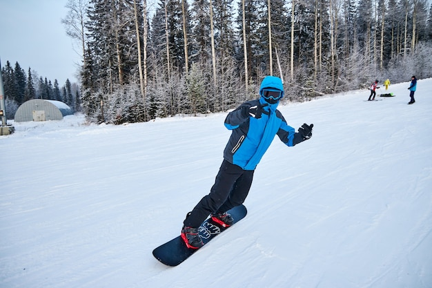 Mensen gaan snowboarden en skiën, winterrecreatie en sporten. op een snowboard de berg af skiën, grappige emoties op de gezichten van mannen en vrouwen